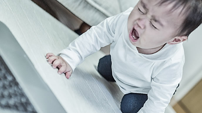 パソコンを前に絶望の表情で泣き叫ぶ赤ちゃん