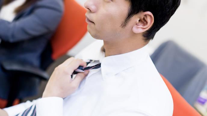 ネクタイを締め直し気合を入れるリーダー