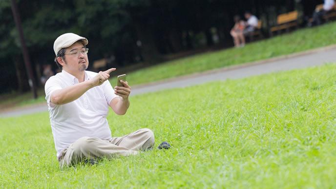 会社の昼休みにスマホで遊ぶ中年男性