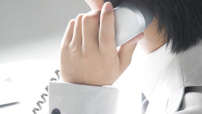 電話口の相手を商談をする男性