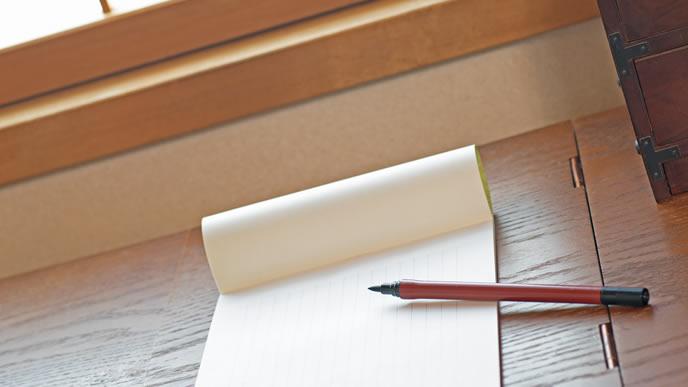 転勤の挨拶を書くための紙とペン