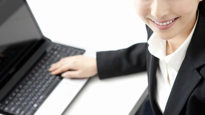 パソコンで転勤の挨拶をするOL