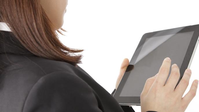 面接する企業をタブレットで調べる就活生
