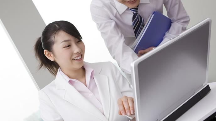 メールの送り方を指導する会社員