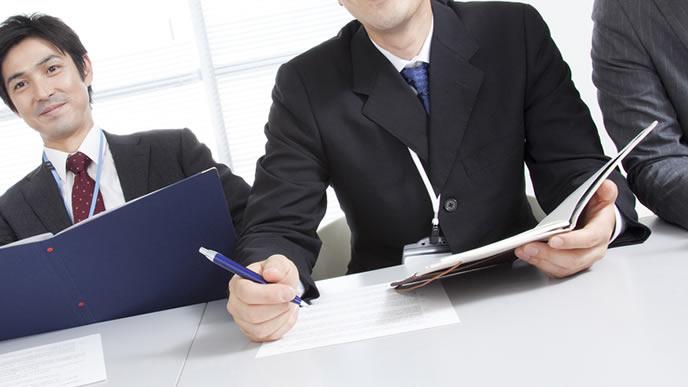 応募者の書類を見ながら面接する担当者