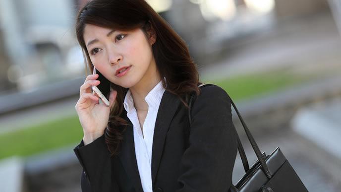 取引先に電話営業をする会社員