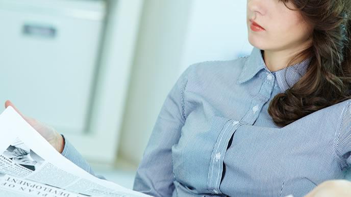 社内報に目を通す女性社員