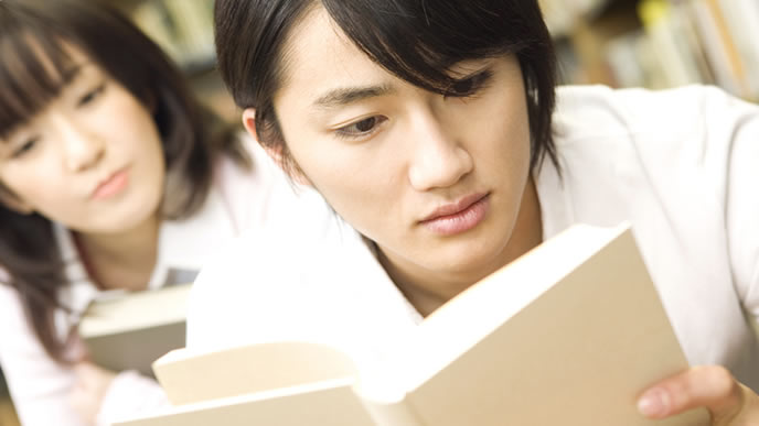 作文の就職試験に自信を付けるために本を読む就活生