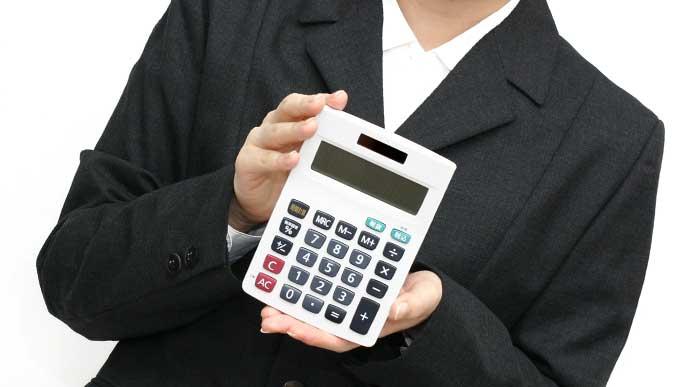 電卓を持っているスーツを着た女性