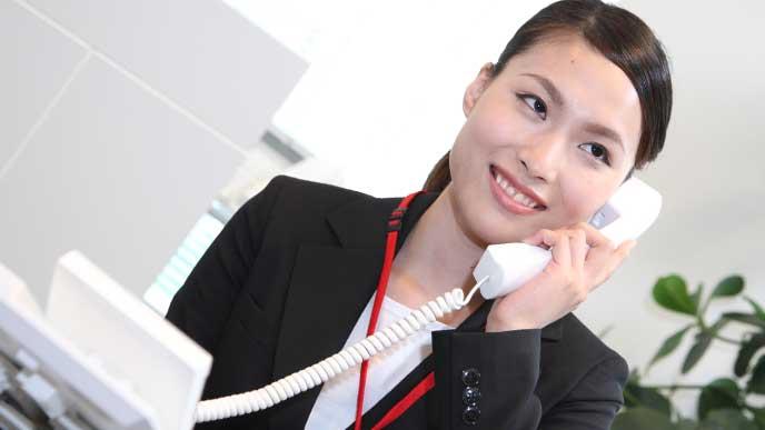 会社で電話をかけているスーツ姿の女性