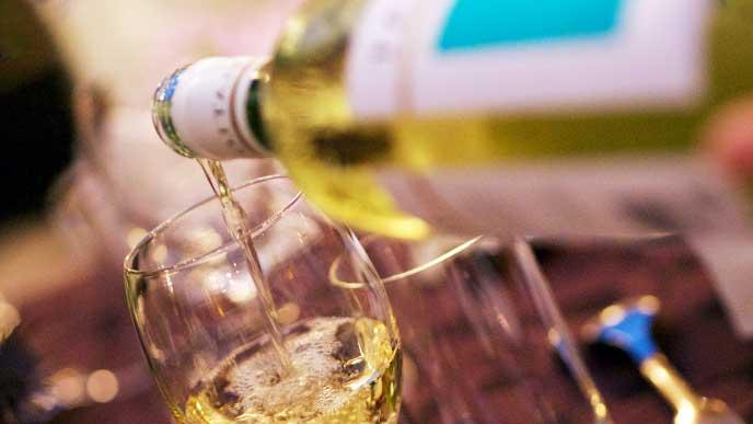 白ワインをグラスに注いでいる