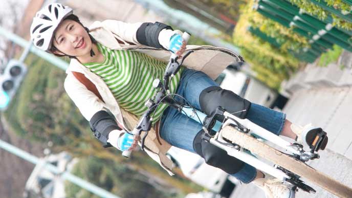 笑顔で自転車通勤しているヘルメットを被った女性