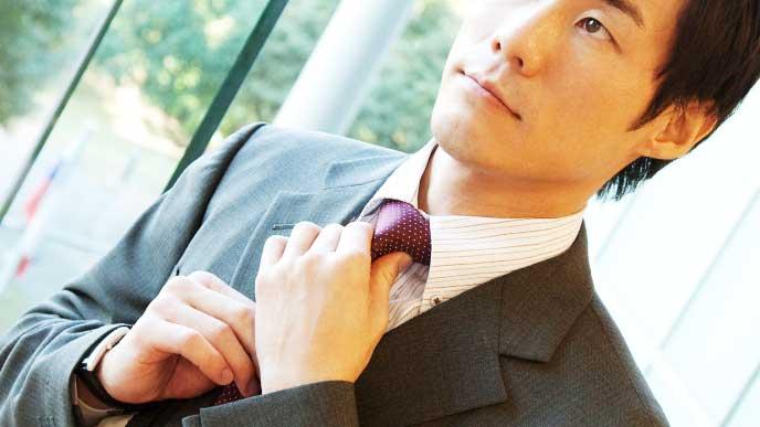 ネクタイを締め直して身だしなみを整えているスーツを着たビジネスマン