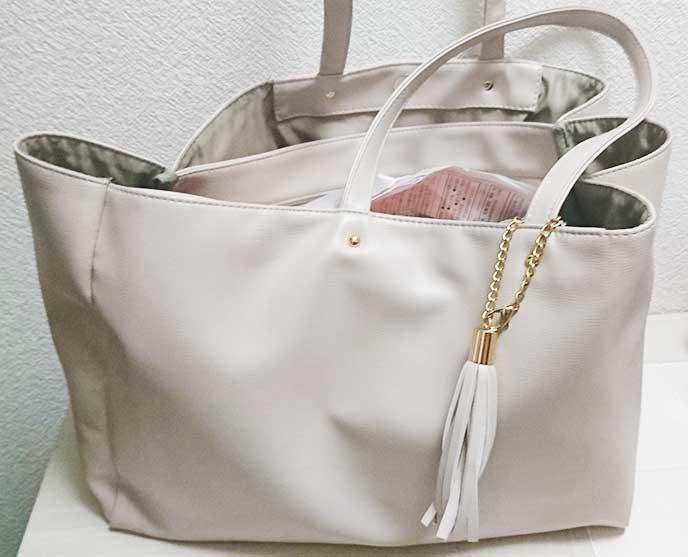 大きなポケットがついた白いトートバッグ