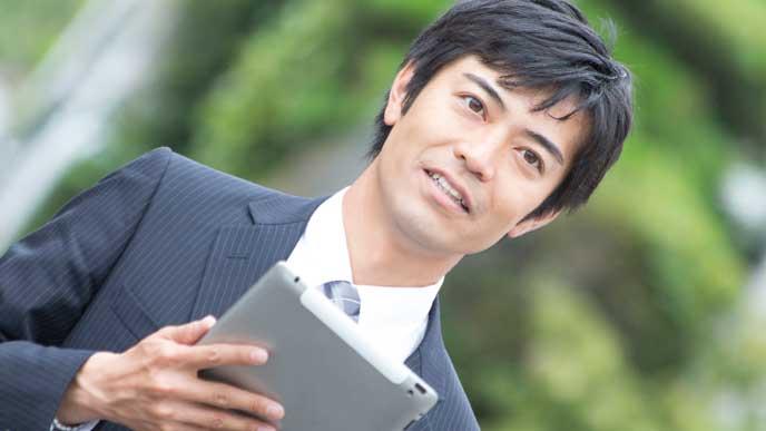アプリで会社までの距離を確認しているスーツを着た男性