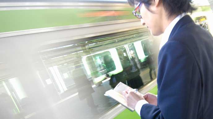 ホームで電車を待ちながら本を読んでる男性