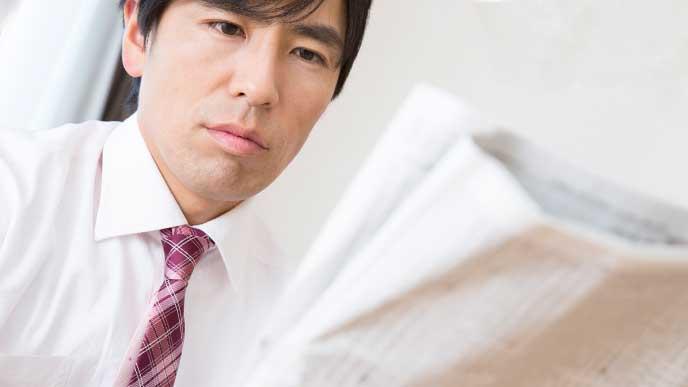 電車の中で新聞を読んでる男性
