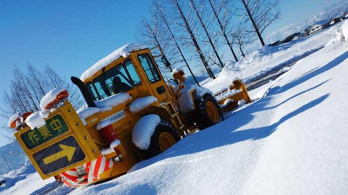 重機を使って除雪をしている季節労働者