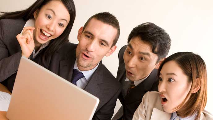 パソコンで社内報を見てる社員たち