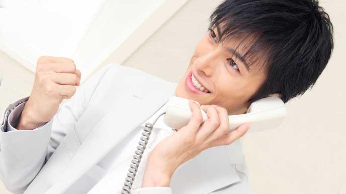 上手く電話に対応できガッツポーズをしているスーツを着た男性