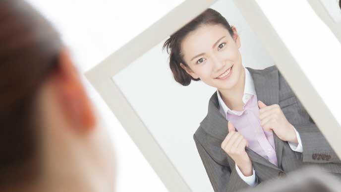 鏡を見ながらスーツに着替える女性