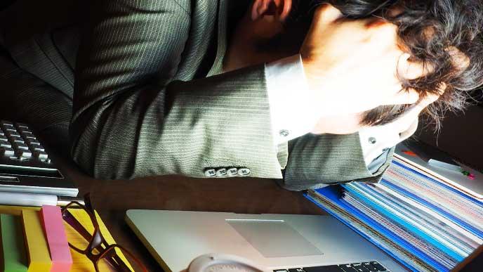 残業に疲れて頭を抱えているスーツを着た男性