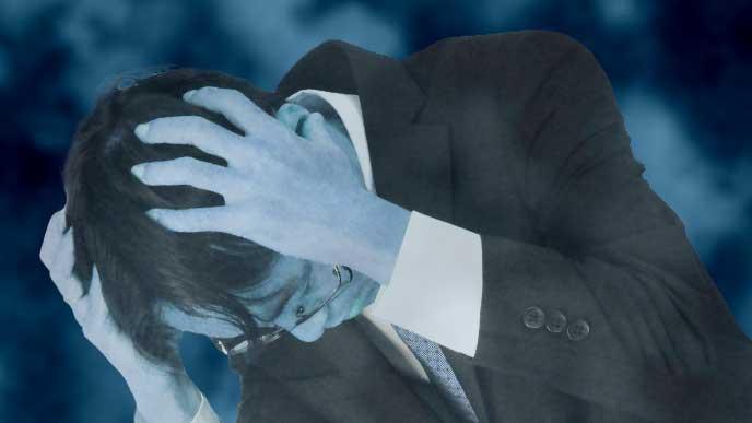 ストレスで頭を抱えているスーツを着た男性