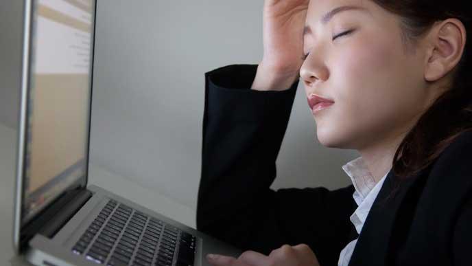 遅くまで残業してPCの前で居眠りしてる女性