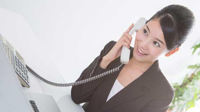 笑顔で電話を受けているスーツを着た女性社員