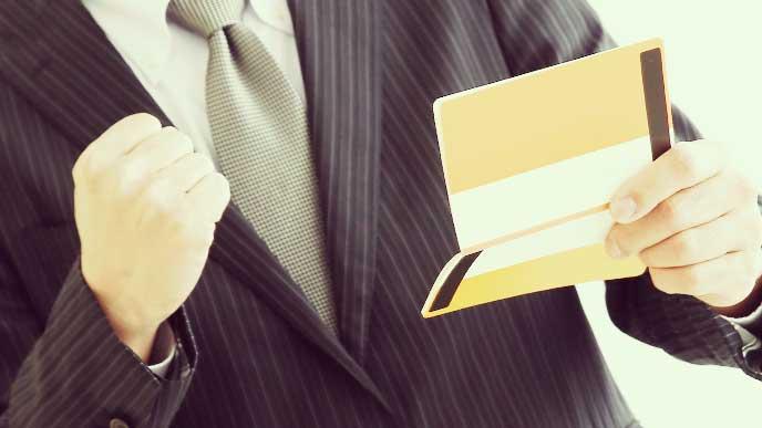 通帳を見てガッツポーズしているスーツを着た男性