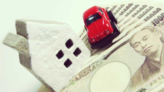 家と車の模型と現金