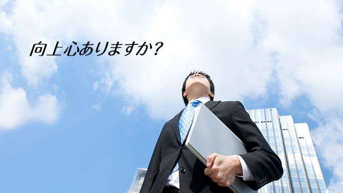 ビジネス街を上を見て歩く男性