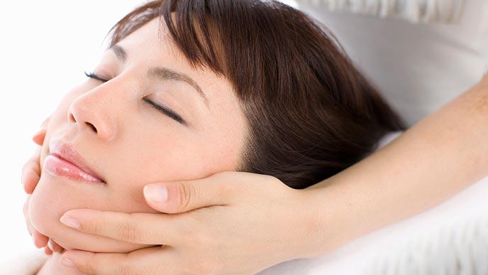 女性の顎をマッサージするエステティシャン
