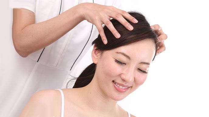 女性の頭皮をマッサージするエステティシャン