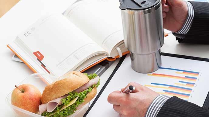 持参したサンドイッチと水筒を机に置くサラリーマン