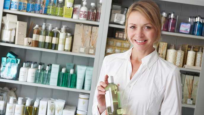 化粧品の棚の前に立つ美容部員