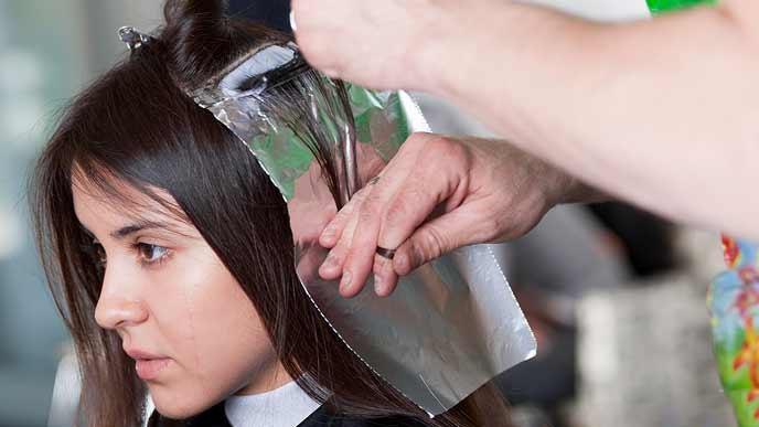 美容院で髪を染める女性