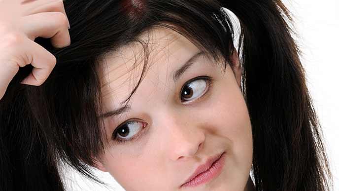 髪の毛の生え際を見つめる女性