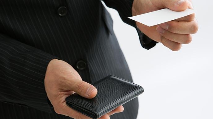 黒の名刺入れを片手に持って名刺を差し出すビジネスマン