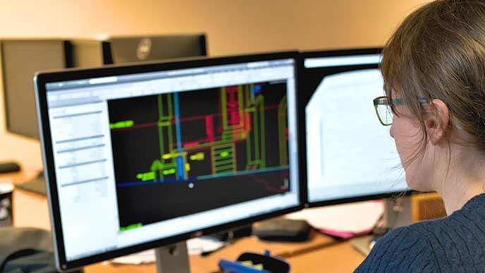 cadソフトで設計図をモニターで作成する女性オペレーター