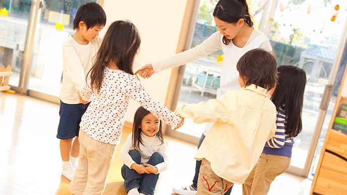 子供たちと円になって手を繋ぐ保育士