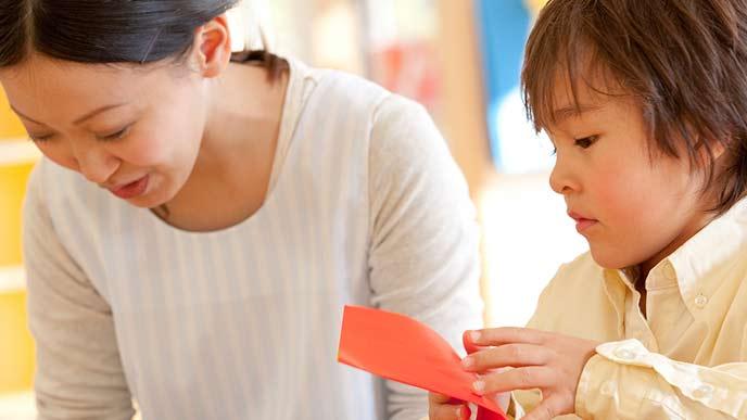 子供に折り紙を教える保育士