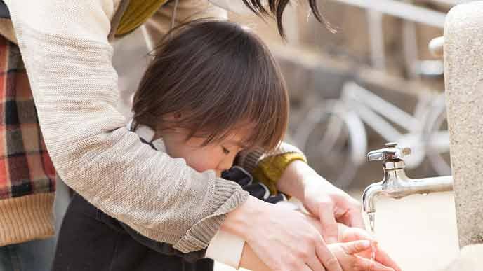 子供の手を洗ってあげる保育士