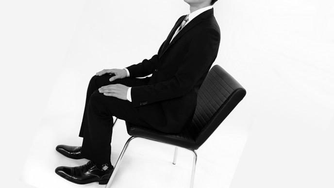 スーツを着て椅子に座る男性