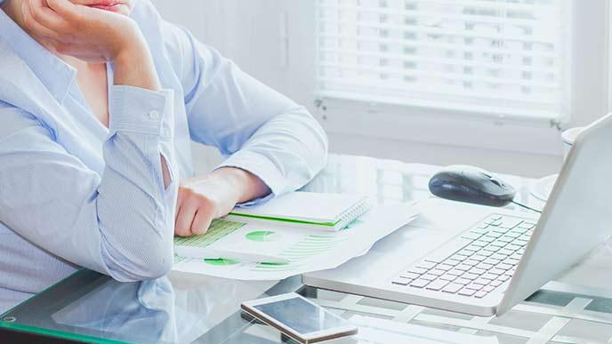 ノートパソコンを見ながら考え込む女性事務員