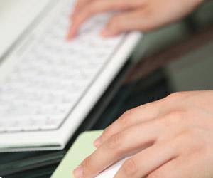 キーボードとマウスを操作する女性の手