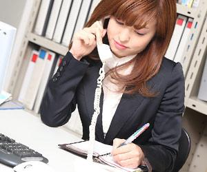電話しながら手帳に書き込む女性事務員