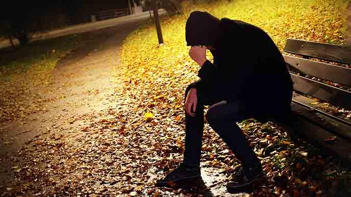 公園のベンチに一人座る男性