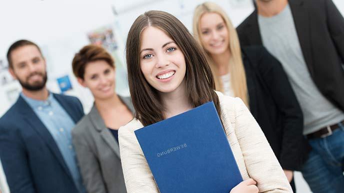大学生がレポートを持って仲間の前に立つ