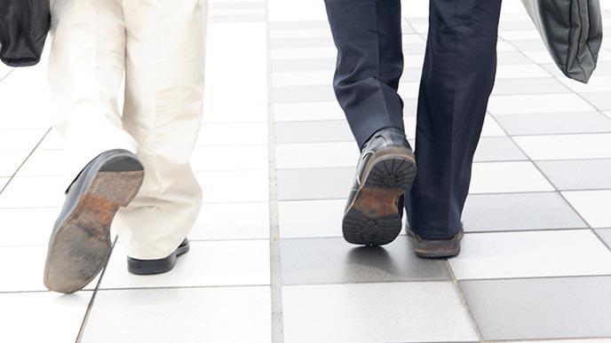 歩道を歩くビジネスマンの足元
